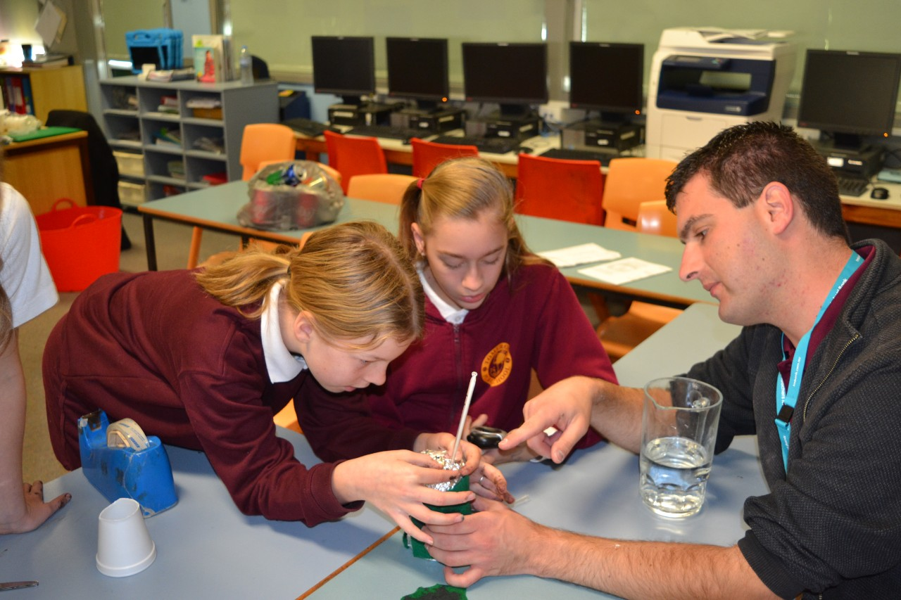 Students with teacher doing science experiment
